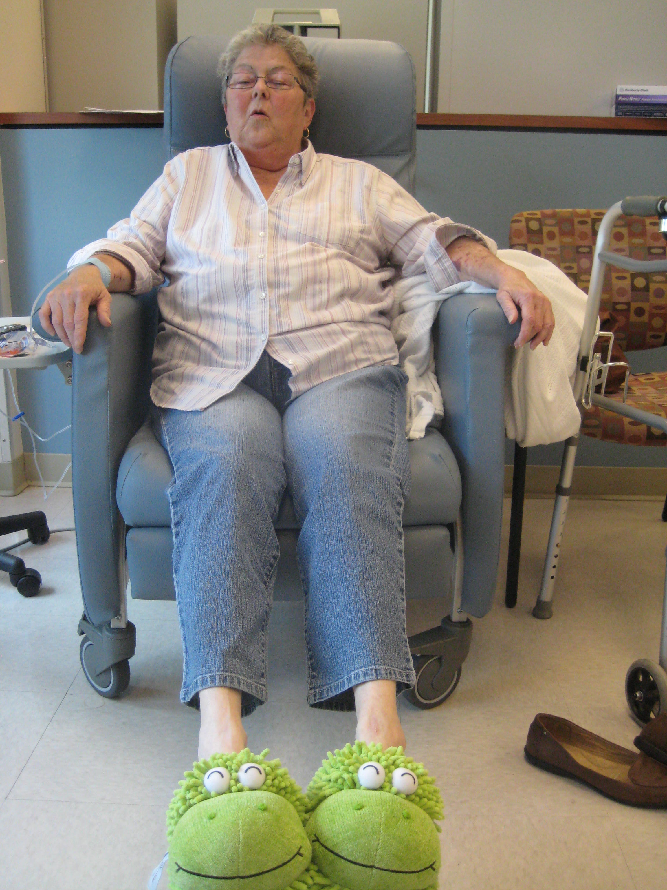 A happy patient takes a load off to warm her feet in a soft pair of fuzzy frog slippers.