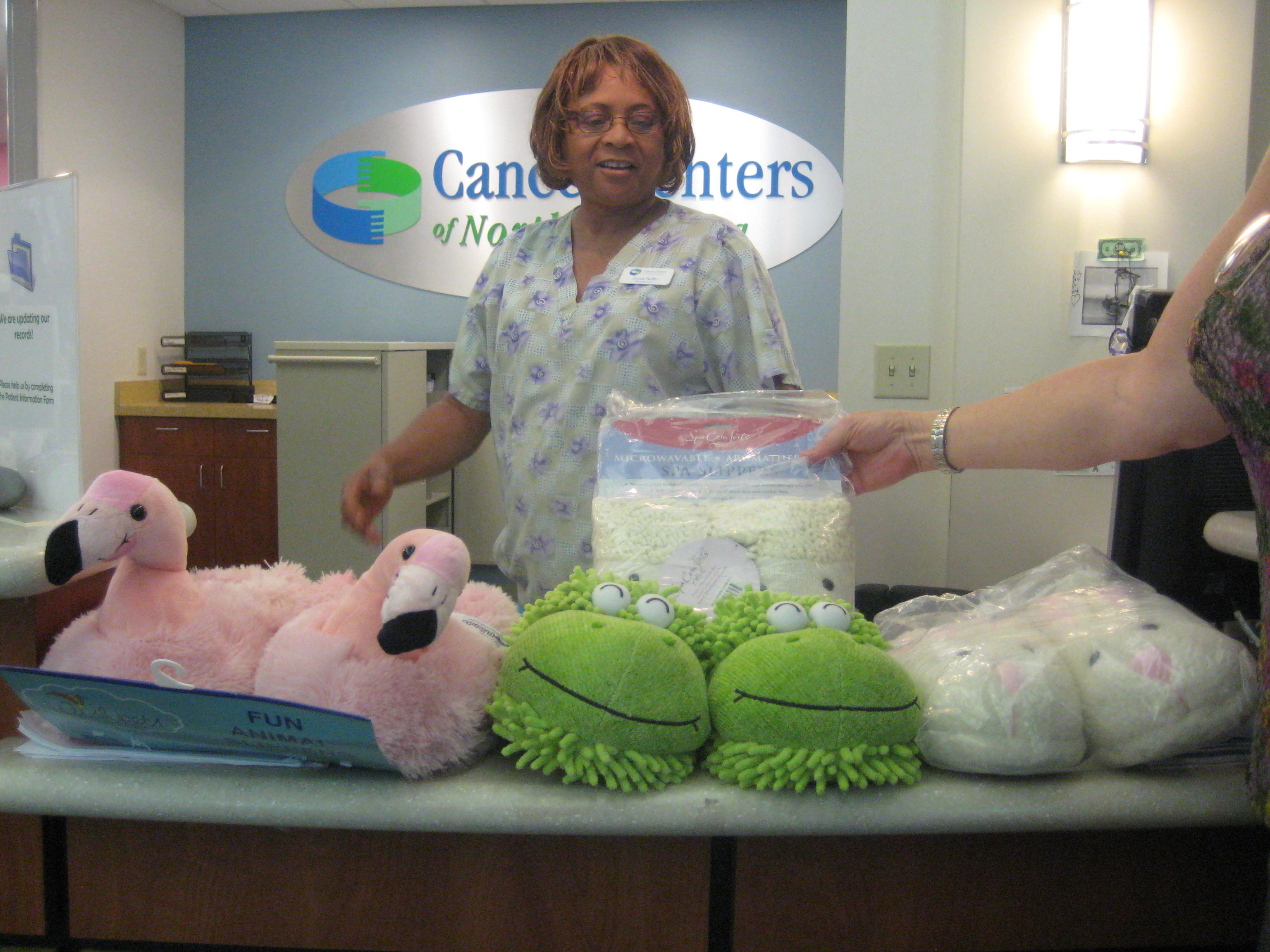 A staff member at the Cancer Centers of North Carolina opens slippers to give to patients.